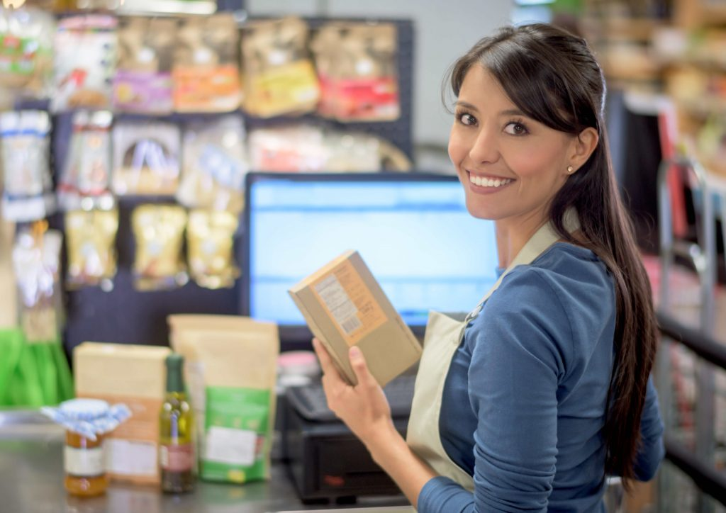 Latin woman working on a cashier at the supermarket and looking at the camera smiling