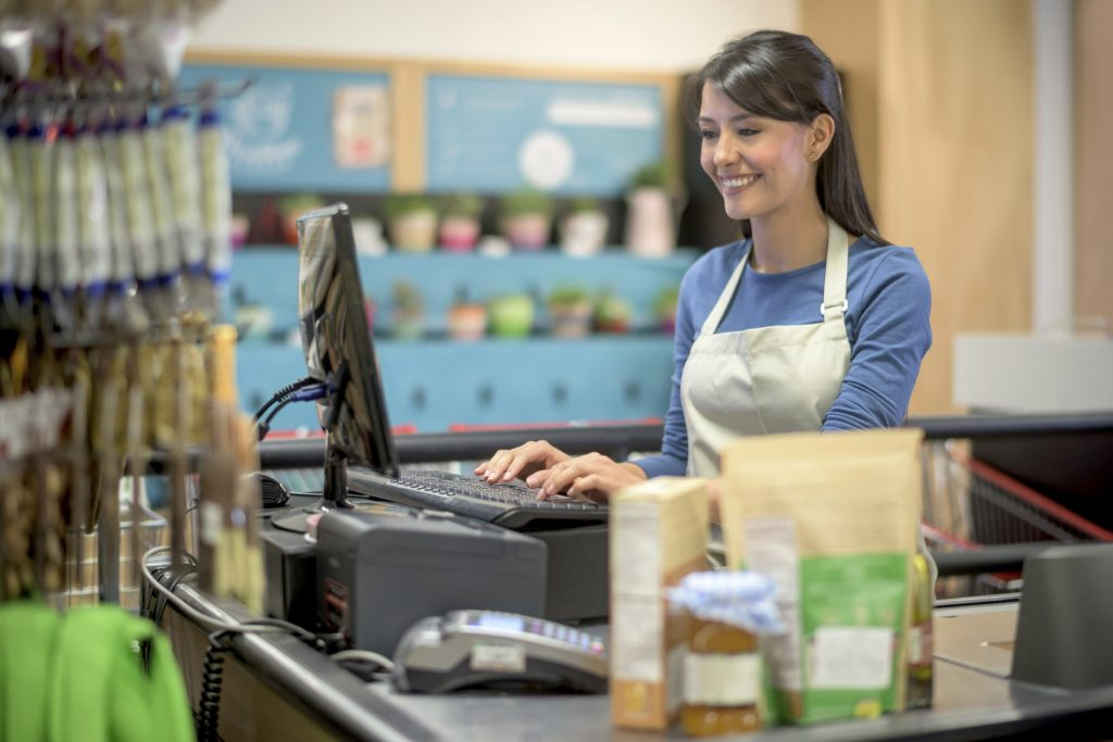 Latin woman working on a cashier at the grocery store and scanning products and smiling